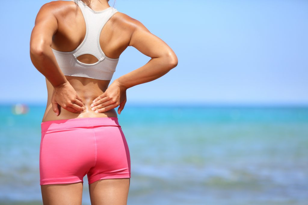 Back pain - Athletic woman rubbing her back